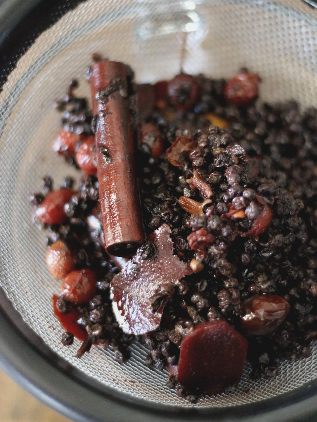 Elderberries and spent fruit in sieve