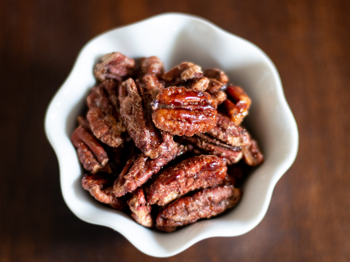 Toasted pecans with a light glaze of spiced maple syrup are a great snack you will love.